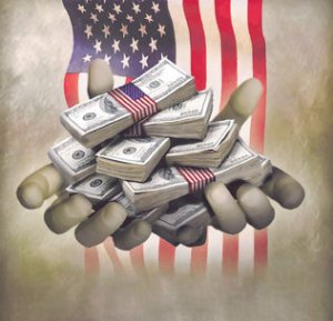 Handfuls_of_dollar_stacks_and_US_flag